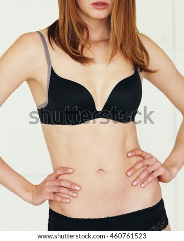 Underwear concept. Young sexy woman with red hair in lingerie posing on white background. Close up - stock photo