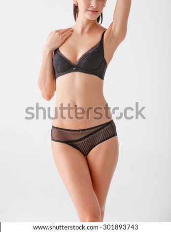 underwear model with black underwear posing on a white background - stock photo
