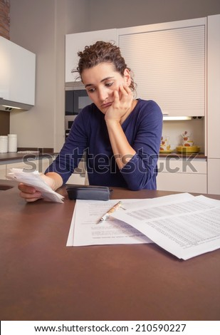 Unemployed and divorced woman with many debts reviewing her monthly bills - stock photo