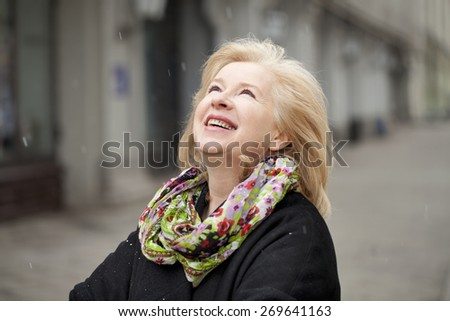 Unexpected snowfall in mid-April, happy portrait of an elderly woman in the street - stock photo