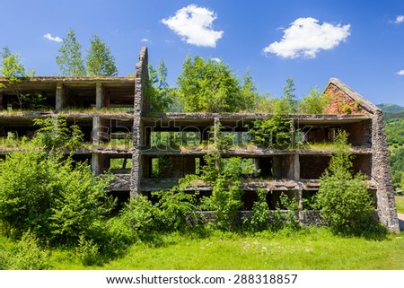 Unfinished abandoned buildings, overgrown plants - stock photo