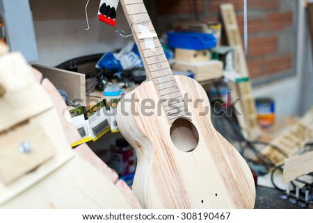 Unfinished acoustic guitar at workshop   - stock photo