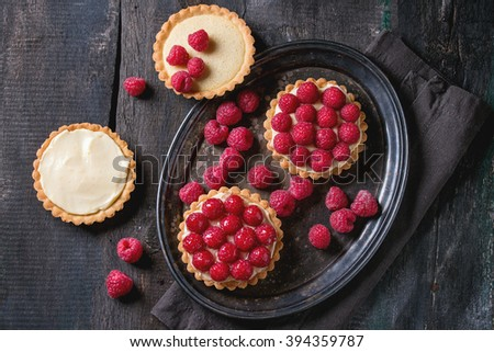 Unfinished and ready to eat tartlets with custard and fresh ripe raspberries, served on vintage metal tray with baking forms and textile napkin over old wooden table. Dark rustic style. Flat lay - stock photo