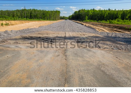 Unfinished asphalt country road in pine forest. Under construction - stock photo