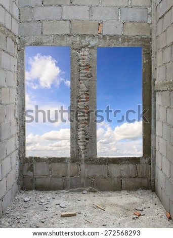 Unfinished brick house with blue sky on window. - stock photo
