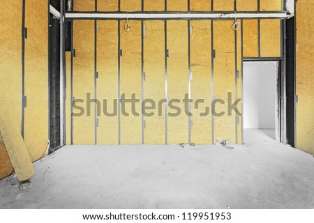 Unfinished building interior, walls covered with rock-wool. - stock photo