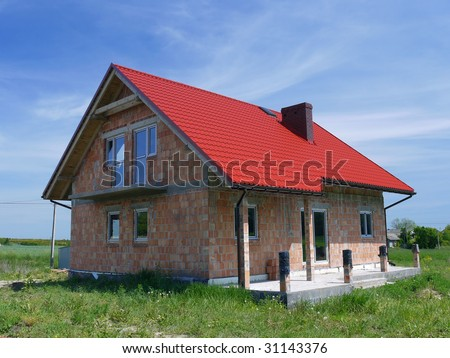 Unfinished single family brick house covered by red sheet for Red brick house with metal roof