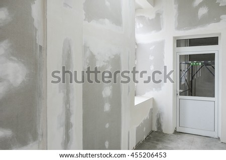 unfinished walls with gypsum and white door - stock photo