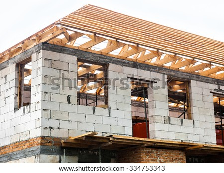 Unfinished white brick house with timber roof truss. - stock photo