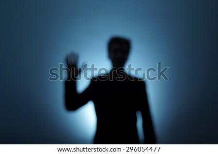 Unfocused backlit man moves his hand to say hello. Near-death experience. Dream image.  - stock photo