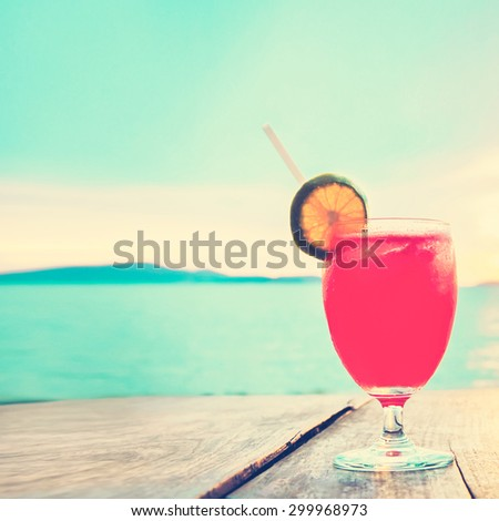 Unfocused cocktail drink on wood table in front of summer sea and sky background, vintage tone - chill out and summer holiday concept - stock photo