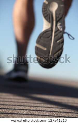 Unfocused man shoes running on the asphalt with the sky in the background - stock photo