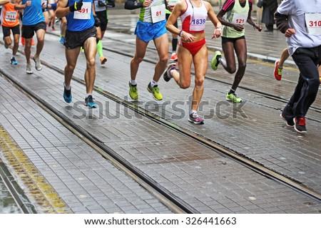 Unfocused Marathon running race in city streets - stock photo
