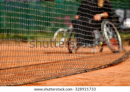 Unfocused wheelchair tennis player is seen behind a tennis net on a clay court - stock photo