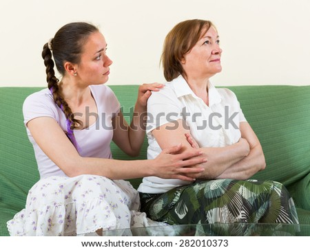 Unhappy adult daughter against mature mother after conflict - stock photo
