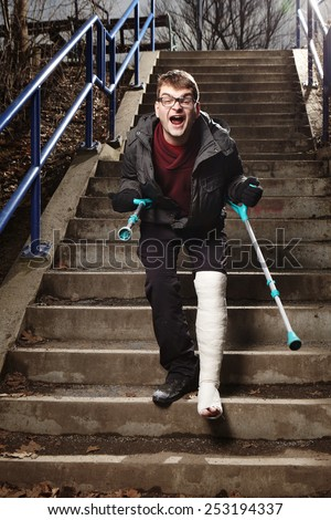 Unhappy and angry man with broken leg in gypsum hardly move on stairs with crutches - stock photo