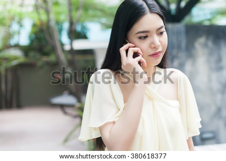 Unhappy Asian woman on phone - relationship and family concept - stock photo