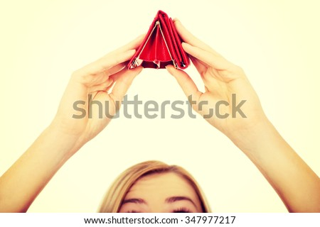 Unhappy bankrupt woman with empty wallet. - stock photo