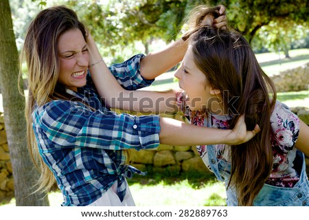 Unhappy blonde girls fighting angry pulling long hair - stock photo