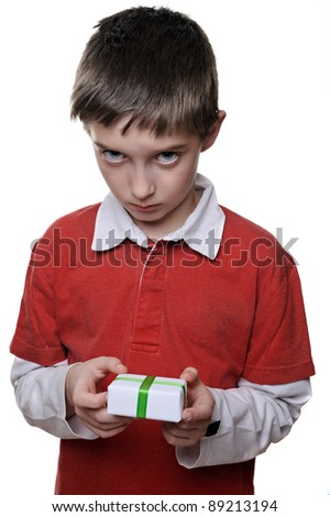 unhappy boy not satisfied about a very small present in his hands - stock photo