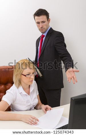 Unhappy business man debating with blond woman business  partner about some data on computer display. - stock photo