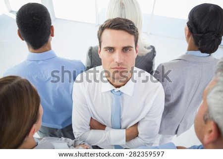 Unhappy businessman looking at camera with his colleague around him in office - stock photo