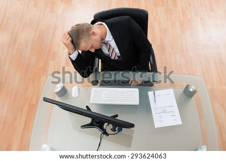 Unhappy Businessman Sitting At Desk In Office - stock photo