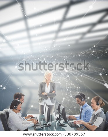 Unhappy businesswoman monitoring her colleagues against white room with windows at ceiling - stock photo