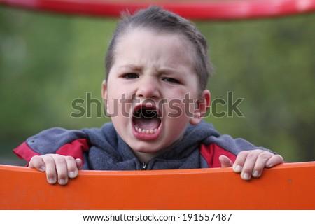 Unhappy child cries - stock photo