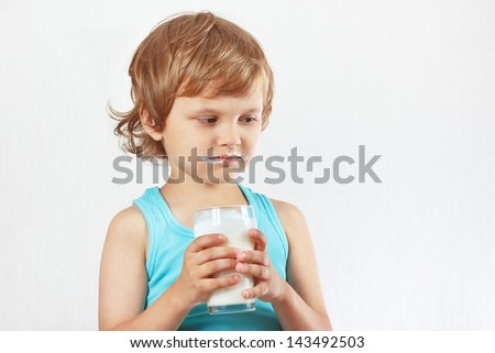Unhappy child does not want to drink a fresh milk - stock photo