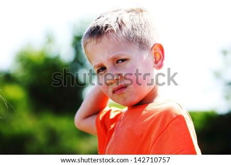 unhappy child expression. Sad little boy outdoor - stock photo