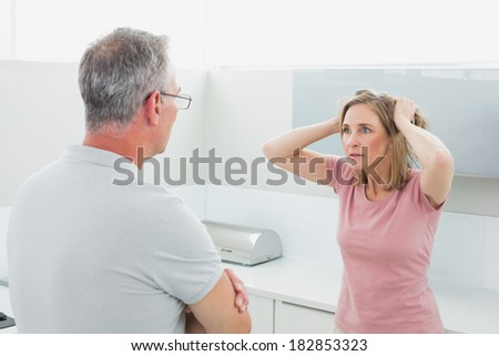 Unhappy couple having an argument in the kitchen at home - stock photo