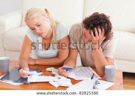 Unhappy couple listing expenses in the living room - stock photo