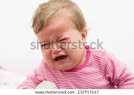Unhappy crying baby girl nine-month looking at the camera. - stock photo