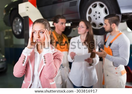 Unhappy female duping by troubleshooters at auto service center - stock photo