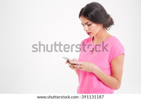Unhappy frowning young woman using smartphone over white background  - stock photo