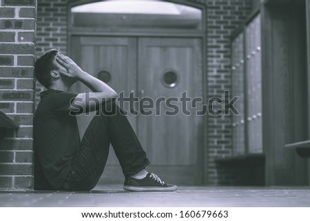 Unhappy handsome student in pain having a headache in school - stock photo