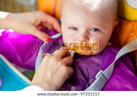 Unhappy infant girl learning to eat solid food - stock photo