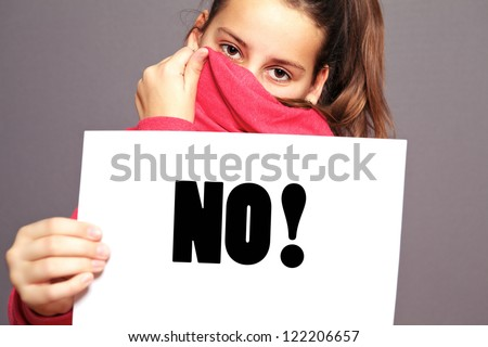 Unhappy little girl hiding behind the collar of her jacket saying an emphatic NO by means of bold type text on a sheet of white paper - stock photo