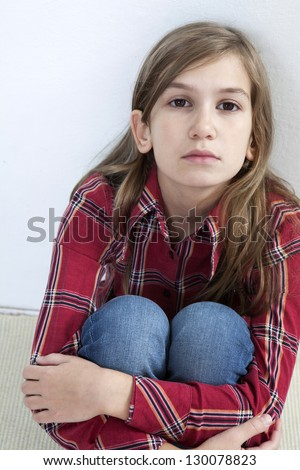 Unhappy little girl sitting on carpet. Problems with parents - stock photo