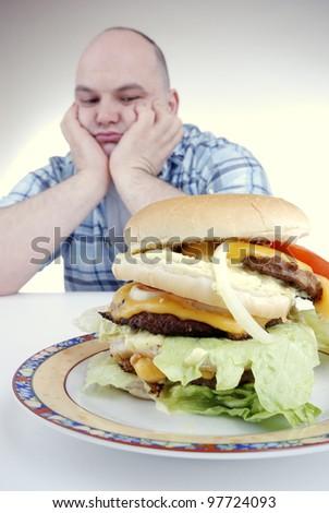 unhappy looking man stares at a big cheeseburger - stock photo