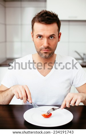 Unhappy man on diet eating a tiny portion of food - stock photo