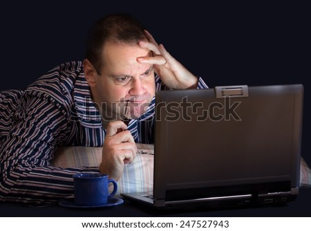 unhappy man with computer in bed - stock photo