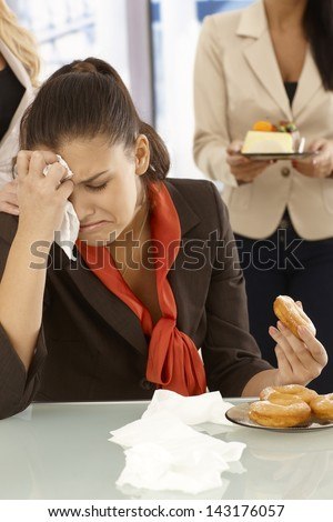 Unhappy office worker sitting at desk, crying, eating doughnut. - stock photo