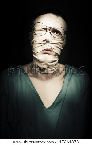 Unhappy Patient With Broken Face Wrapped In Tourniquet Dressing Expressing Distress In A Depiction Of Post Traumatic Stress Disorder PTSD - stock photo