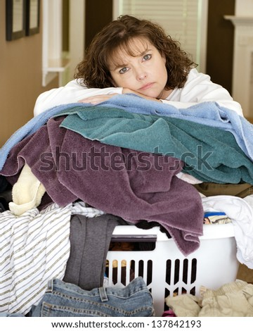 Unhappy, sad, tired woman resting on large, messy pile of laundry - stock photo