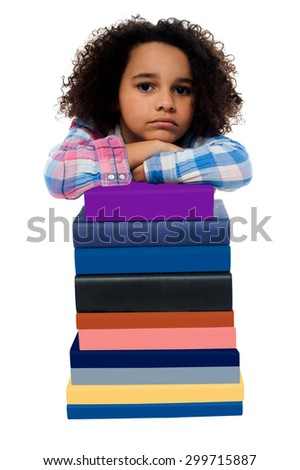 Unhappy school girl with stack of books - stock photo