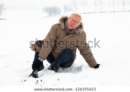 Unhappy senior man with injured painful leg on snow. - stock photo