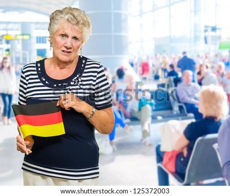 Unhappy Senior Woman Holding Germany Flag, Indoors - stock photo