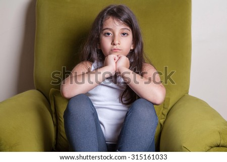 Unhappy small beautiful middle eastern girl with white t-shirt and black hairs looking at camera. - stock photo